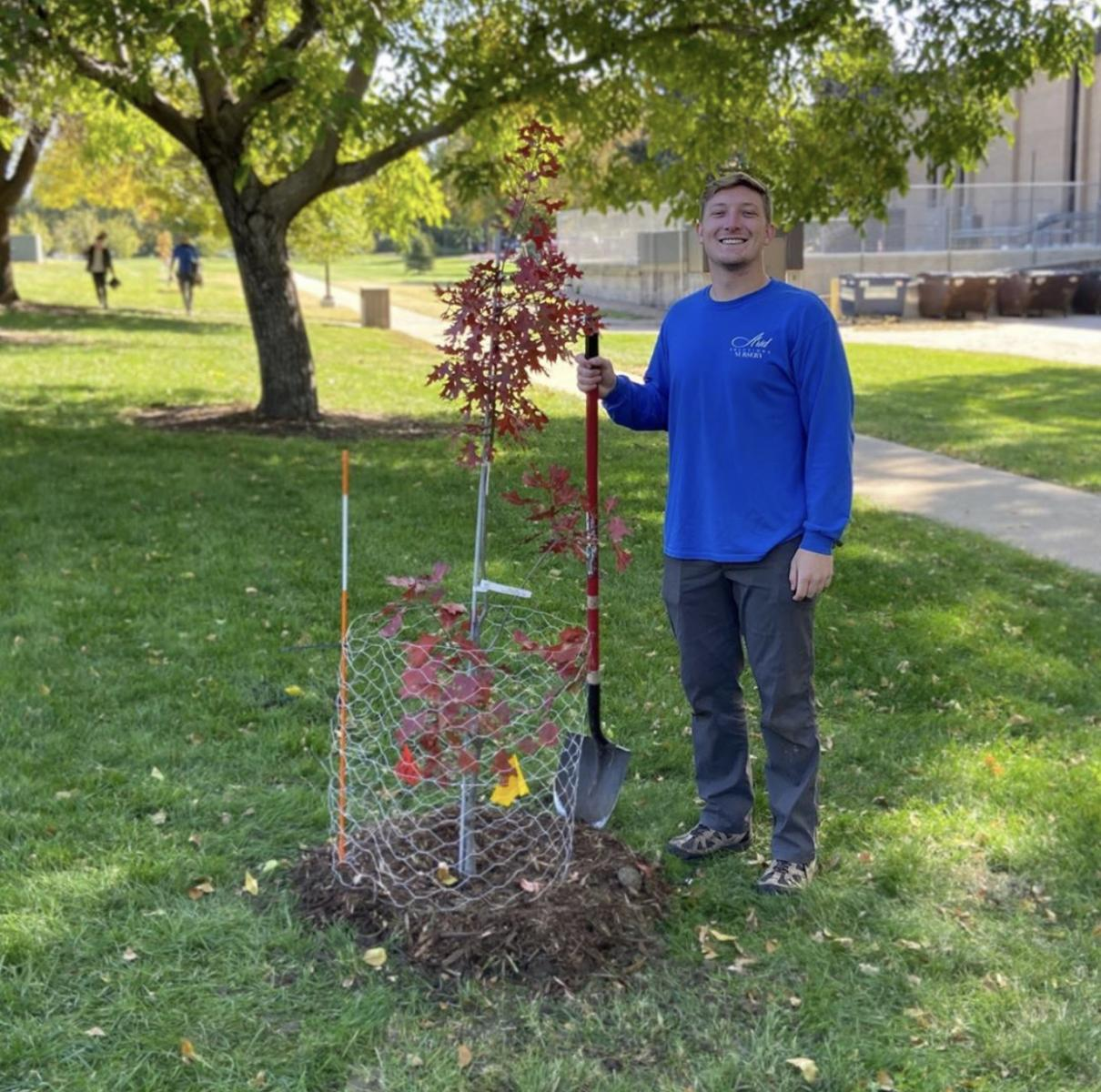 Students stands near freshly planted maple tree for the University of Nebraska's 150th year
