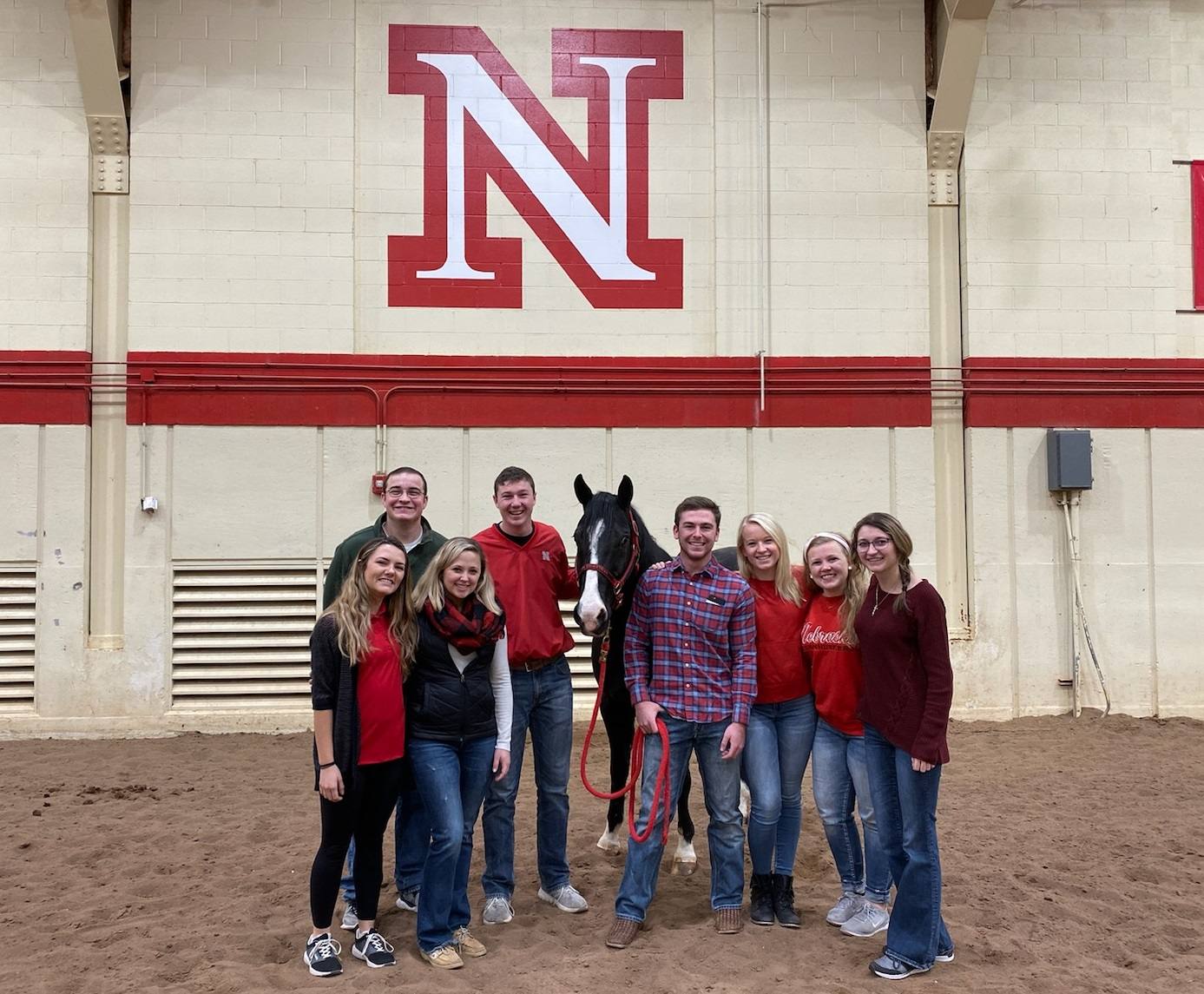 CASNR Ambassadors stand with a horse in animal science arena
