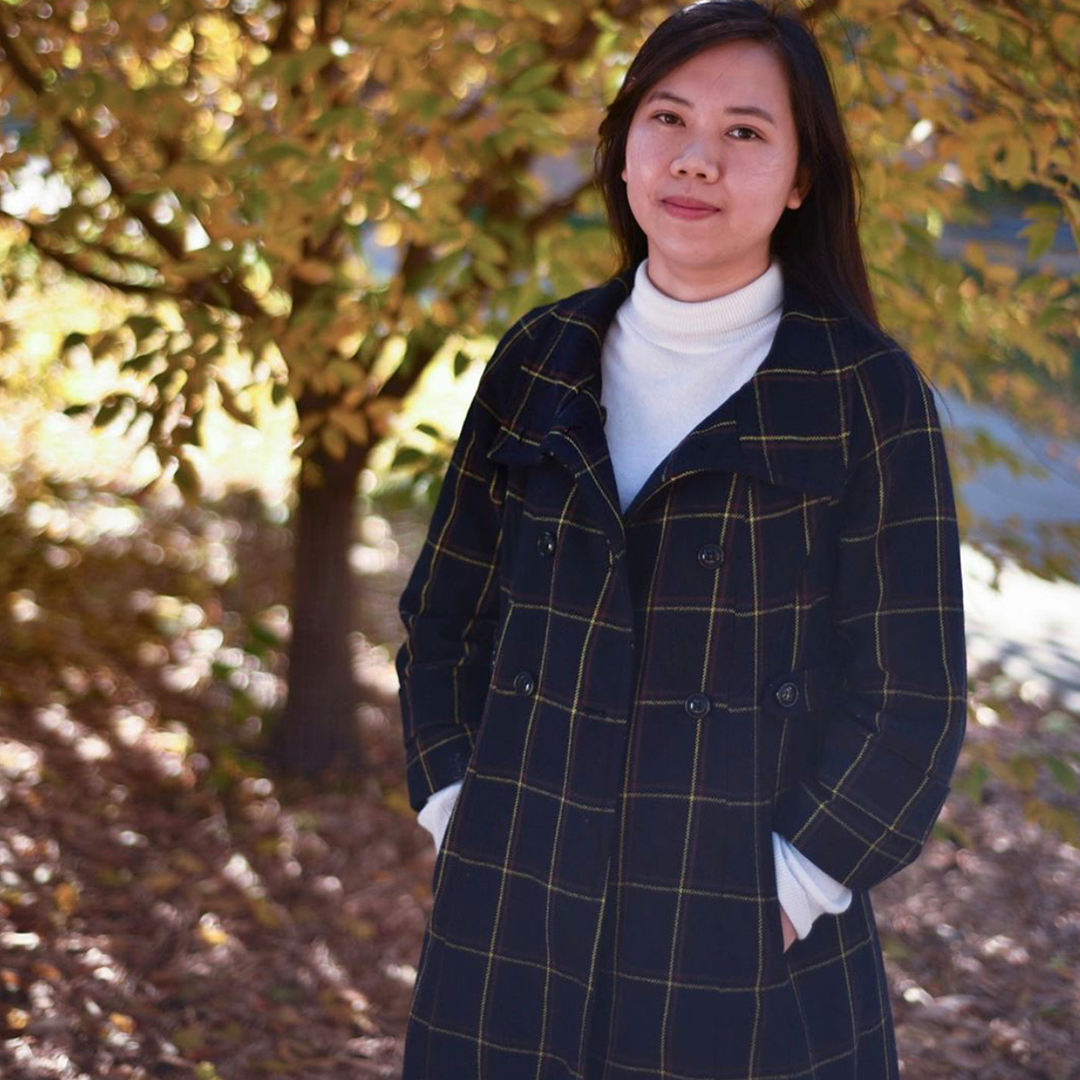 Horticulture student Mia Luong stands in front of tree with autumn colored leaves