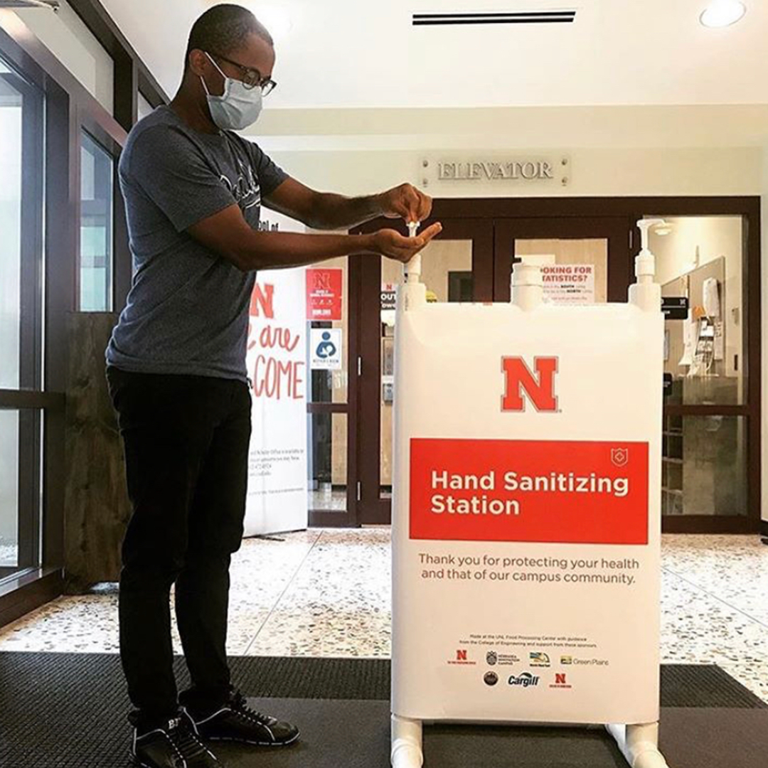 Student with face mask uses the hand sanitizer station on campus