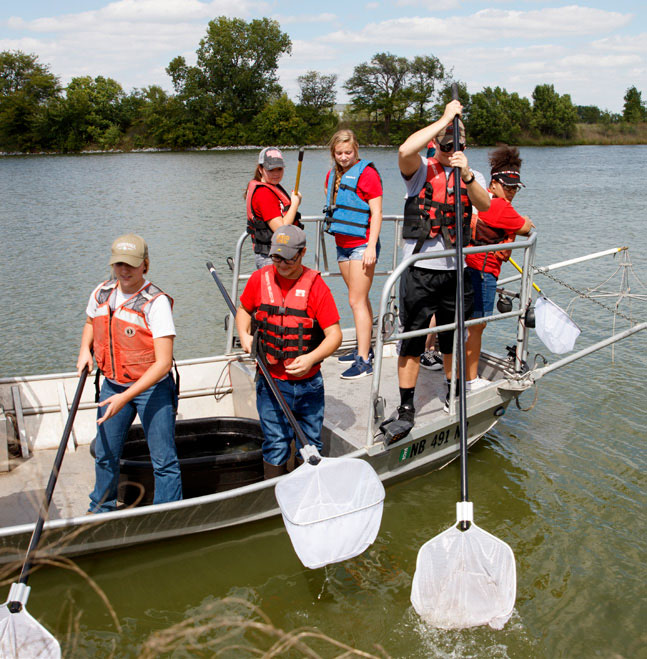 Students collecting specimens in a boat