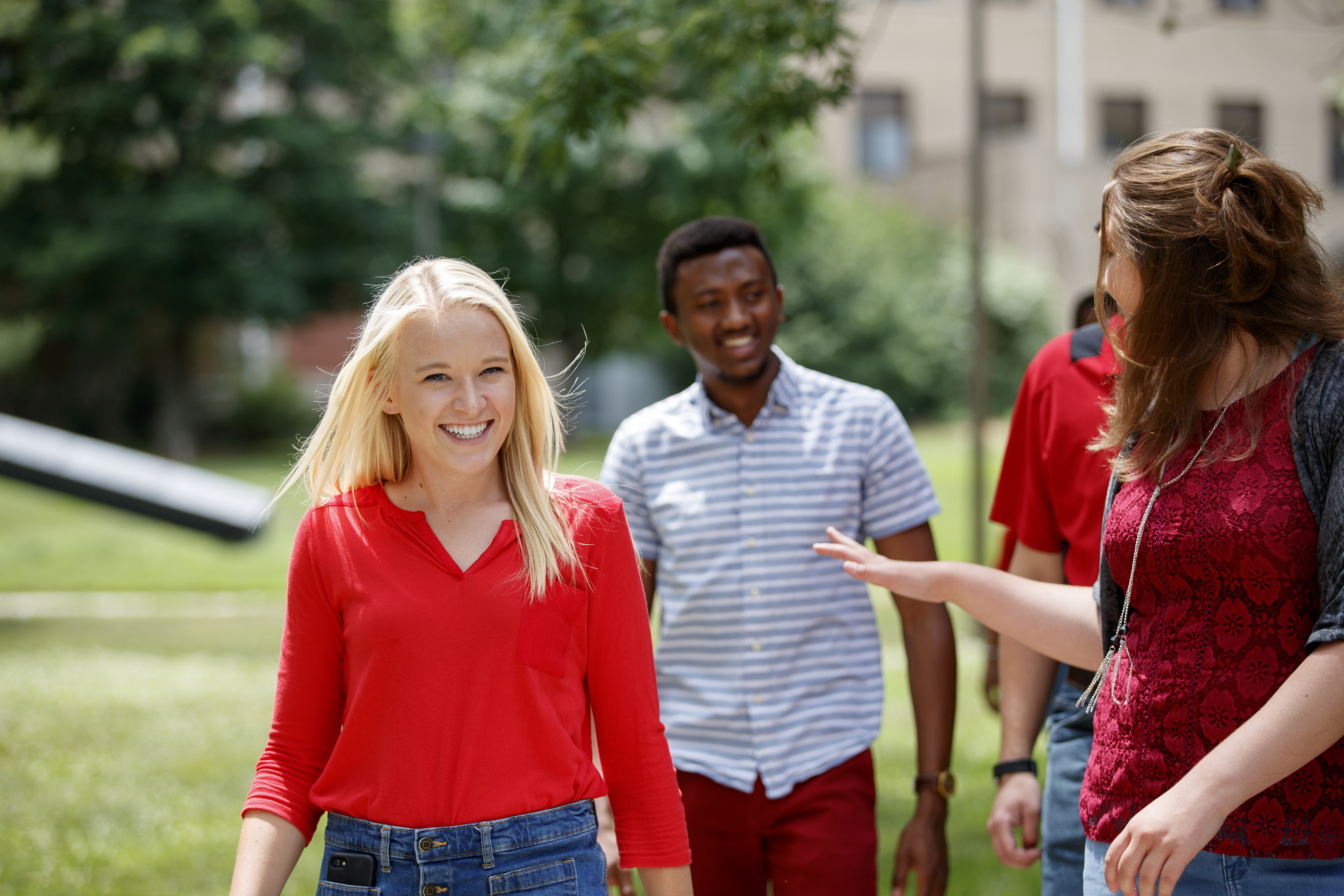 Three students converse and laugh while walking around East Campus