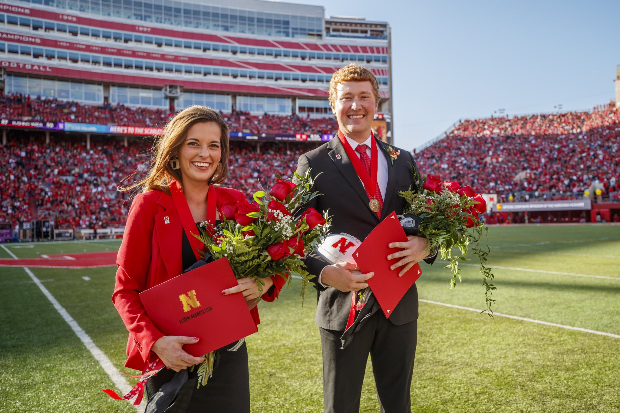 2019 Homecoming Queen and King stand with flowers and medals in the middle of the football field at halftime