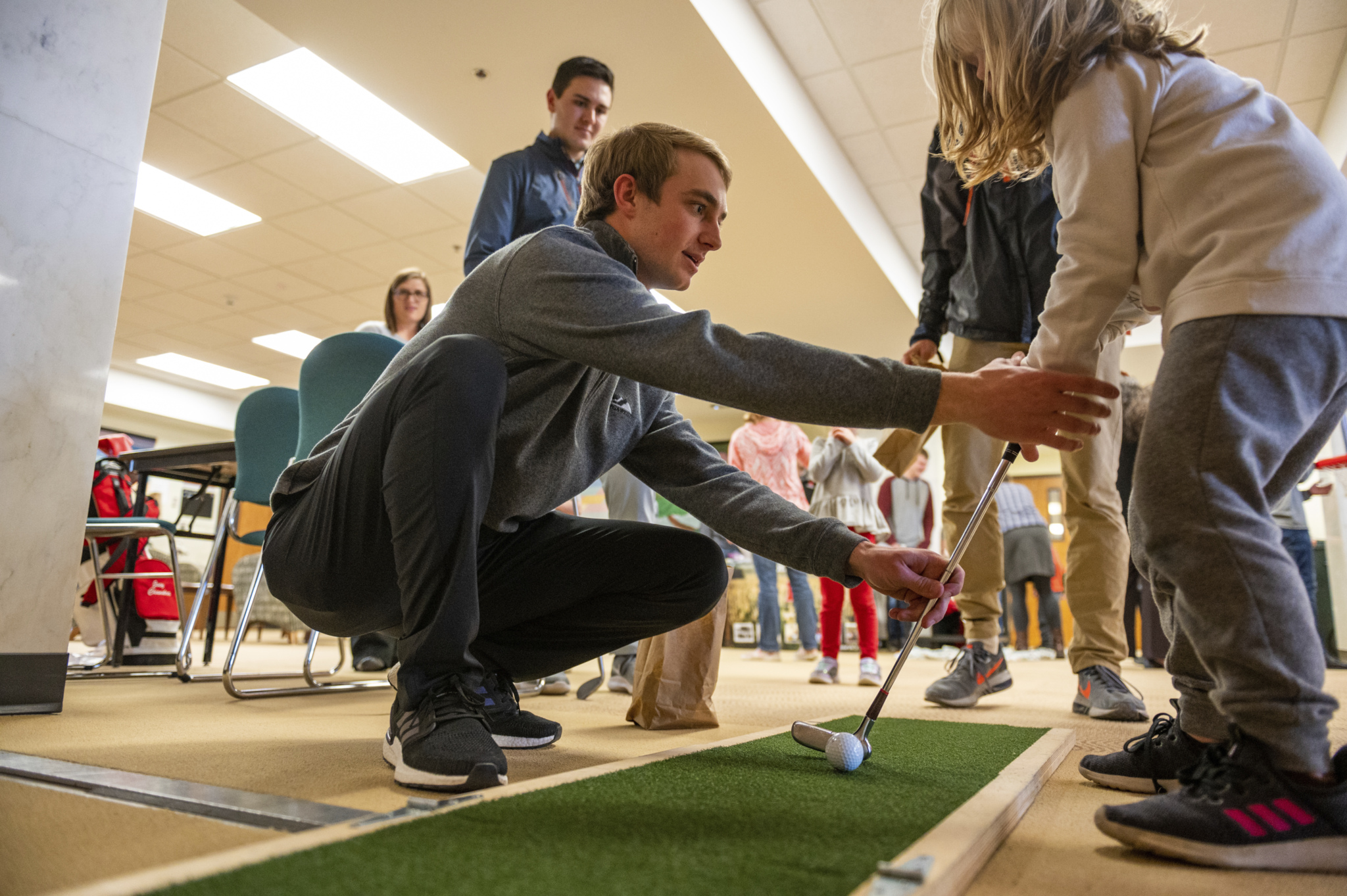 A professional golf management student demonstrates proper putting techniques to a child during CASNR Community night