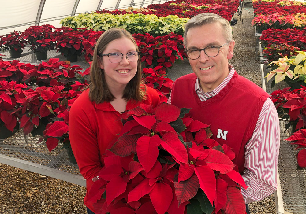 Horticulture Club president Christine Barta and Chancellor Ronnie Green hold poinsettia plant in front of them